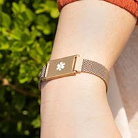 Woman wearing brushed sandstone plated stainless Urban Medical Alert bracelet with mesh chain and affixed ID tag with white caduceus.