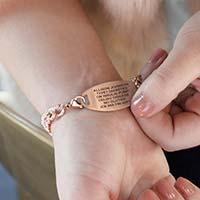 Woman showing custom laser engraved medical alert tag in rose gold