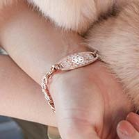 Woman showing rose gold tone medical alert tag with decorative etching