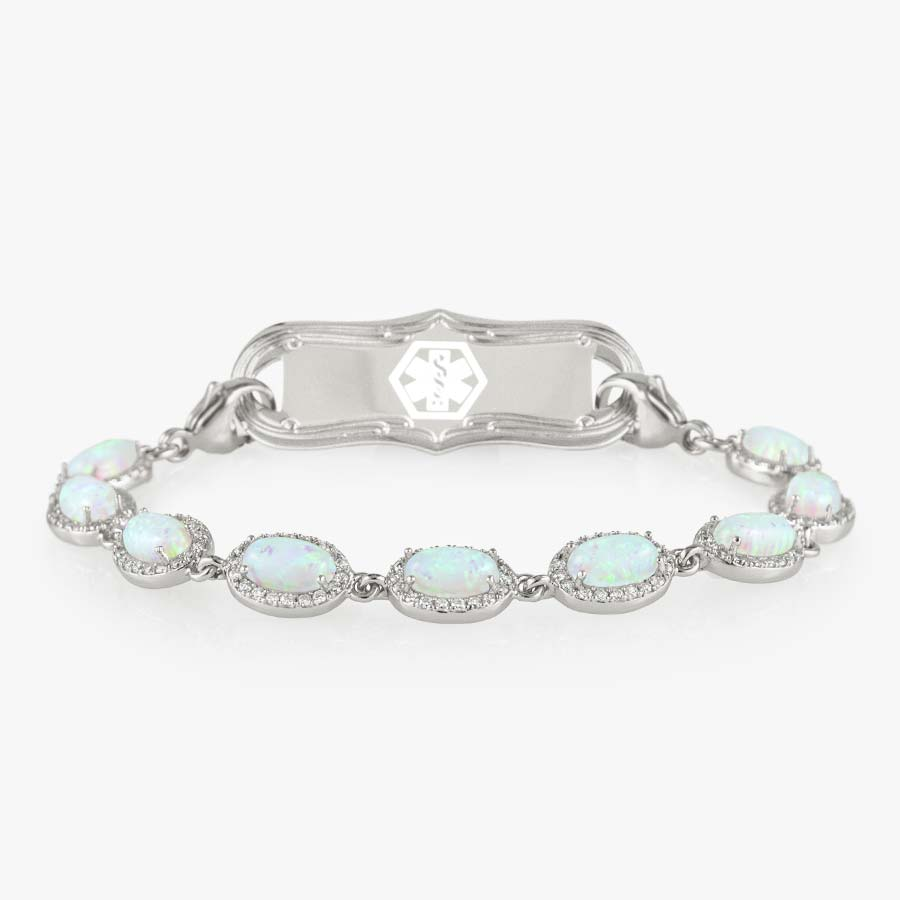 Bracelet with repeating links of simulated opals and czs. Shown with a silver tone tag with white med symbol.