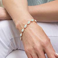 Woman wearing the Opal Medical ID Bracelet in Sterling Silver with natural oval-shaped opals and cubic zirconia accents