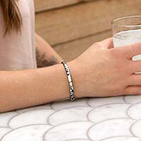 Woman wearing silver and black leather medical ID bracelet and holding a cup