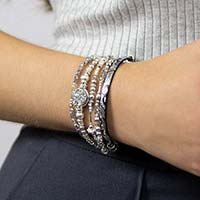 Woman wearing silver beaded medical ID bracelet with silver and black leather medical ID bracelet