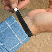 Man wearing black mesh magnetic medical ID bracelet with white caduceus showing magnetic clasp.