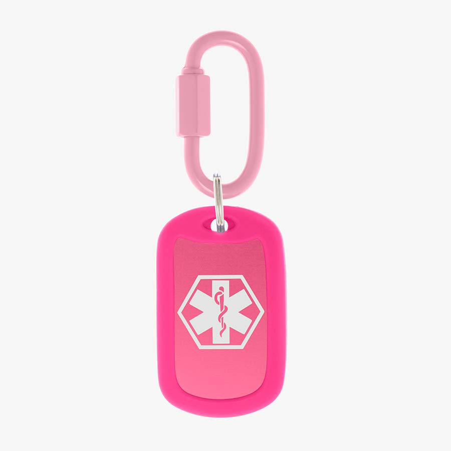 Bright pink aluminum bag tag with white medical symbol and coordinating silicone silencer on matching carabiner clip.